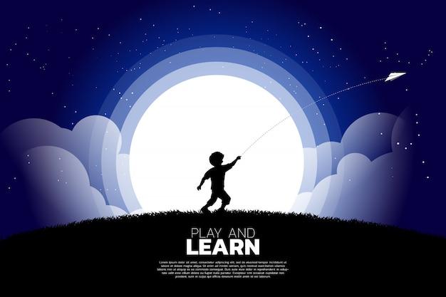 Chłopiec biegnie rzucić samolot papieru origami w nocy. Premium Wektorów