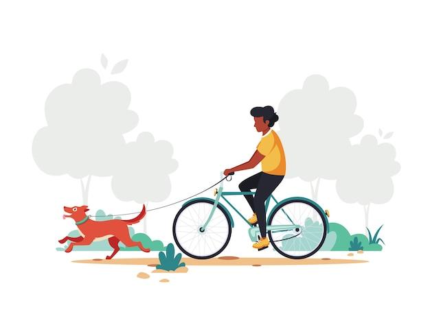 Czarny Człowiek Jedzie Na Rowerze Z Psem W Parku. Premium Wektorów
