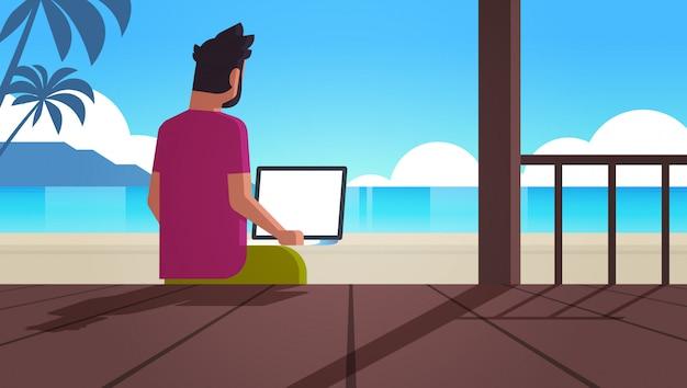 Człowiek Korzysta Z Laptopa Na Tropikalnej Plaży Wakacje Letnie Komunikacja Online Blogowanie Koncepcja Bloger Widok Z Tyłu Siedzi Na Drewnianym Tarasie Pejzaż Morski Premium Wektorów