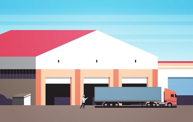 Człowiek pomaga wjechać dużą ciężarówką na parking magazynu Premium Wektorów