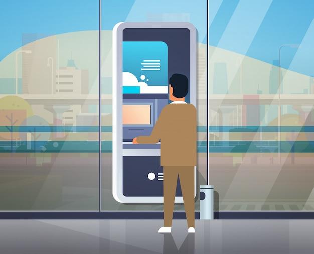 Człowiek za pomocą bankomatu samoobsługowego Premium Wektorów
