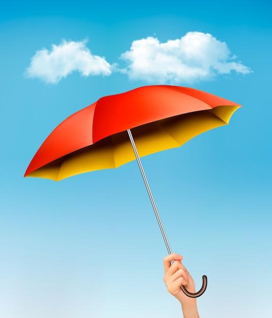 Dłoń Trzymająca Parasol Czerwony I żółty Na Tle Błękitnego Nieba Z Chmurami. Premium Wektorów