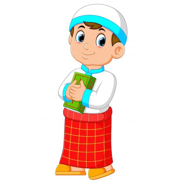 Dobry Chłopiec Z Czerwonym Sarongiem Trzyma Swój Zielony Koran Na Tej Skrzyni Premium Wektorów