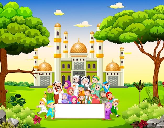 Duża szczęśliwa rodzina trzyma pusty transparent w pobliżu meczetu Premium Wektorów