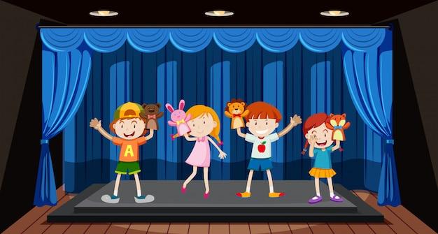 Dzieci bawią się na scenie kukiełką Premium Wektorów