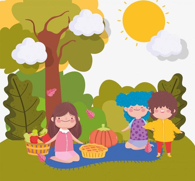 Dzieci z jedzeniem na kocu w parku Premium Wektorów