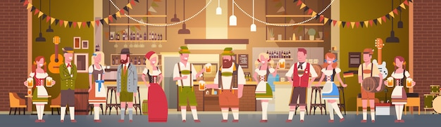 Grupa ludzi pije piwo w barze oktoberfest partyjnego świętowania mężczyzna i kobiety jest ubranym tradycyjnego odzieżowego fest pojęcie Premium Wektorów