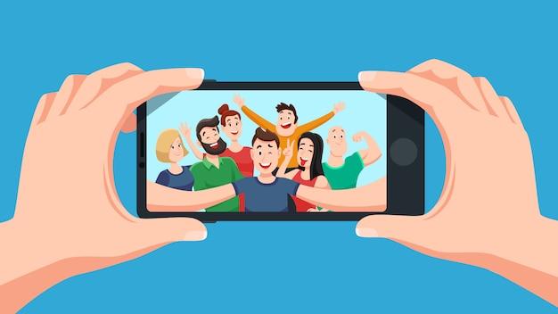 Grupowe selfie na smartfonie. zdjęcie portret przyjaznej drużyny młodzieżowej, przyjaciele robią zdjęcia na kreskówce z aparatu w telefonie Premium Wektorów