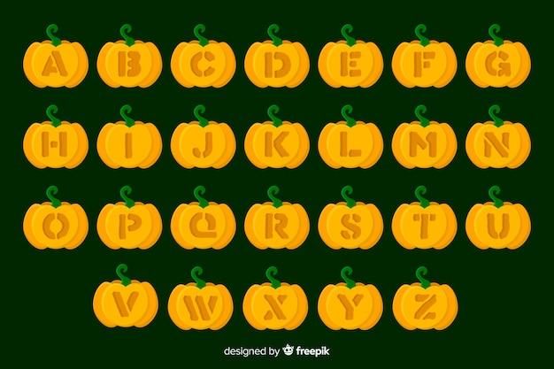 Halloweenowy dyniowy abecadło na zielonym tle Darmowych Wektorów