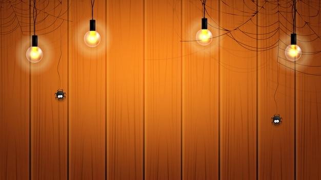 Happy halloween tło z żarówki i pajęczyna na drewnianej ścianie z wiszącymi pająkami. Premium Wektorów