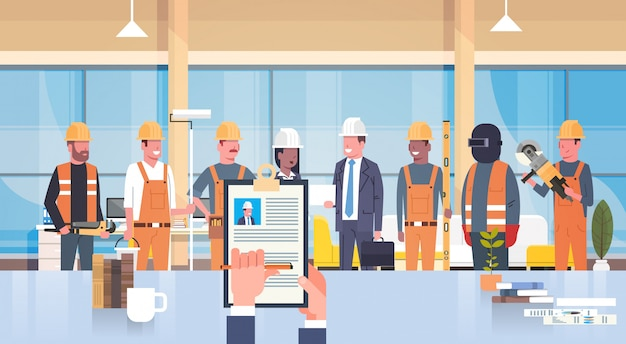 Hr manager hand hold cv cv pracownika budowlanego nad grupą budowniczych wybierz kandydata na va Premium Wektorów