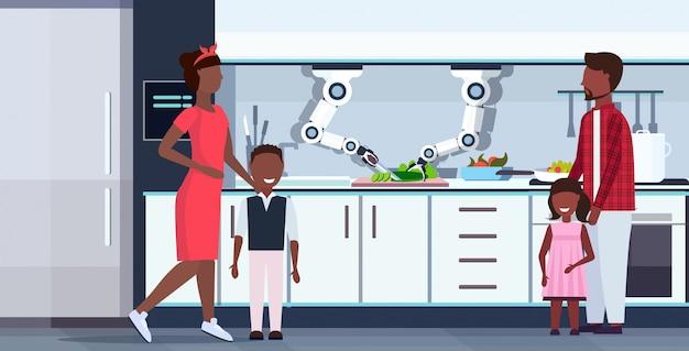 Inteligentny Przydatny Szef Kuchni Robot Tnący Ogórek Na Pokładzie Robot Asystent Innowacja Technologia Sztuczna Inteligencja Koncepcja Szczęśliwa Rodzina Stojący Razem Nowoczesna Kuchnia Wnętrze Poziome Premium Wektorów