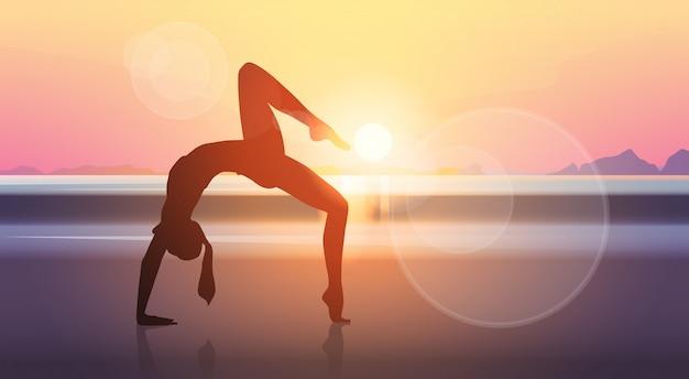 Joga sporta sprawności fizycznej kobiety ćwiczenia treningu sylwetek dziewczyny morza zmierzchu tło Premium Wektorów