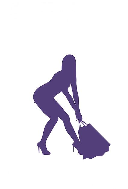 Kobieta niesie wiele torba na zakupy odosobnionej sylwetki żeńskie sprzedaży pojęcie Premium Wektorów