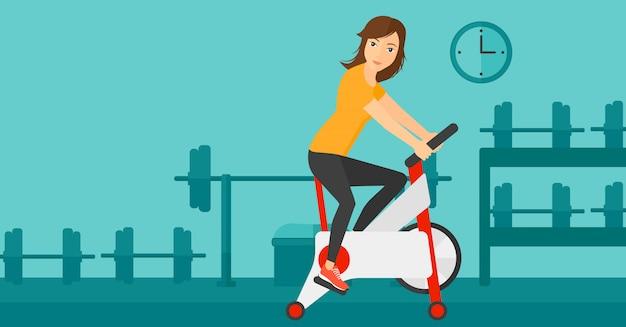 Kobieta robi ćwiczenia na rowerze Premium Wektorów