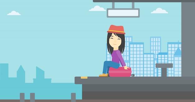 Kobieta siedzi na walizce na dworcu. Premium Wektorów