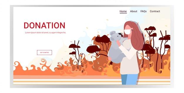 Kobieta W Masce Gospodarstwa Niedźwiedź Koala Pożary Lasów Zwierzęta Ginące W Pożarze Bushfire Klęska żywiołowa Modlić Się Za Australii Koncepcja Intensywne Płomienie Pomarańczowy Portret Kopia Przestrzeń Premium Wektorów