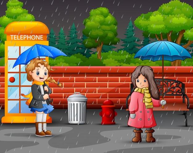 Kreskówka dwie dziewczyny przewożących parasol Premium Wektorów