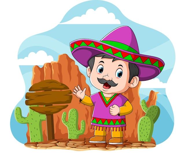 Kreskówka Meksykańskiego Wujka Stojącego W Pobliżu Znaku Drogowego I Kaktusa Premium Wektorów