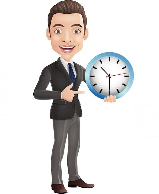 Kreskówka szczęśliwy młody biznesmen trzyma ściennego zegar i wskazuje Premium Wektorów