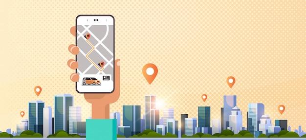 Ludzką Ręką Za Pomocą Zamawiania Online Taxi Udostępnianie Aplikacji Mobilnej Koncepcja Transportu Usługi Udostępniania Samochodu Aplikacja Ekran Smartfona Z Mapą Gps Nowoczesny Pejzaż Miejski Premium Wektorów