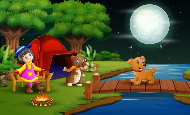 Mała dziewczynka obozuje w lesie przy nocą z jej zwierzęciem domowym Premium Wektorów