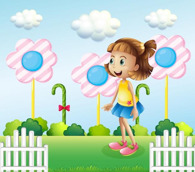 Mała dziewczynka w pobliżu drewnianego ogrodzenia z gigantycznymi cukierkami Darmowych Wektorów
