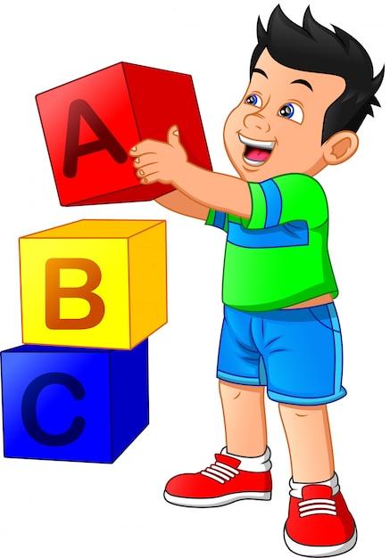 Mały Chłopiec Bawi Się Z Bloku Alfabetu Premium Wektorów