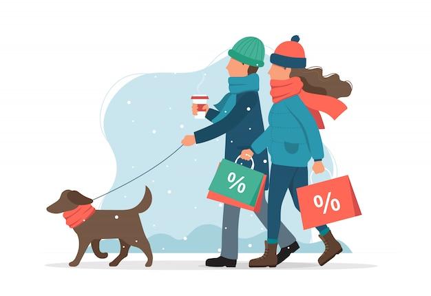 Mężczyzna i kobieta z torby sprzedaży, spacery z psem w zimie. Premium Wektorów