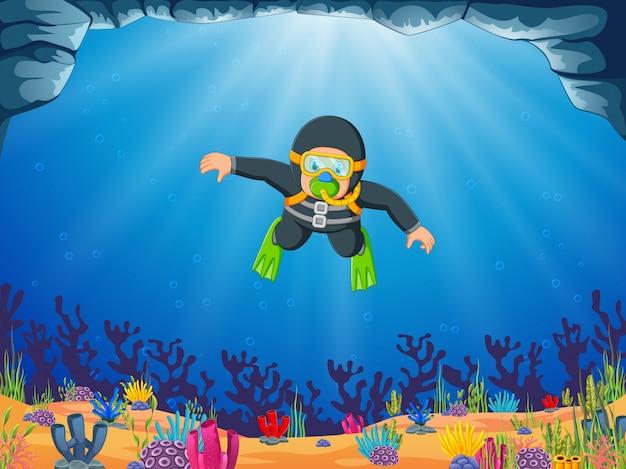 Mężczyzna nurkuje pod błękitnym morzem z żółtymi okularami do pływania Premium Wektorów