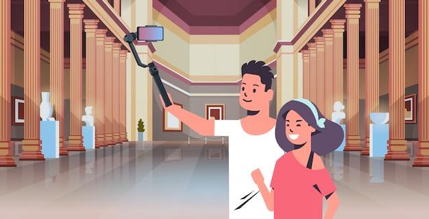 Młoda Para Za Pomocą Selfie Kij Biorąc Zdjęcie Na Smartfonie Aparat Kobieta Mężczyzna Gości W Galerii Sztuki Nowoczesnej Galerii Muzeum Wnętrze Portret Poziomy Premium Wektorów