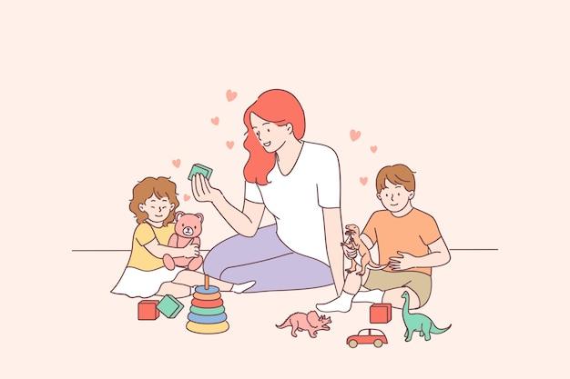 Młoda Uśmiechnięta Nauczycielka I Szczęśliwe Maluchy Dzieci Chłopiec I Dziewczynka Budują Piramidę Za Pomocą Obręczy W Przedszkolu Lub W Domu Premium Wektorów