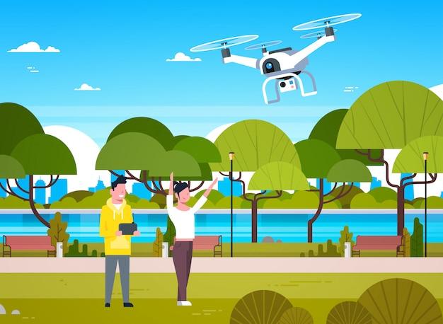 Młodzi ludzie bawią się z drone copter w parku mężczyzna i kobieta za pomocą pilota do quadrocoptera Premium Wektorów