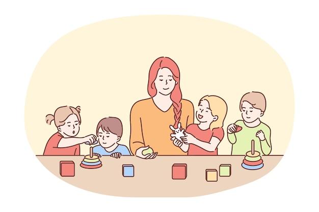 Niania W Przedszkolu, Opiekunka, Koncepcja Opieki Nad Dziećmi. Młoda Uśmiechnięta Kobieta Postać Z Kreskówki Opiekunka Do Dziecka Lub Niania Bawi Się Z Grupą Małych Dzieci Przy Stole. Siostra, Matka, Rodzicielstwo Premium Wektorów