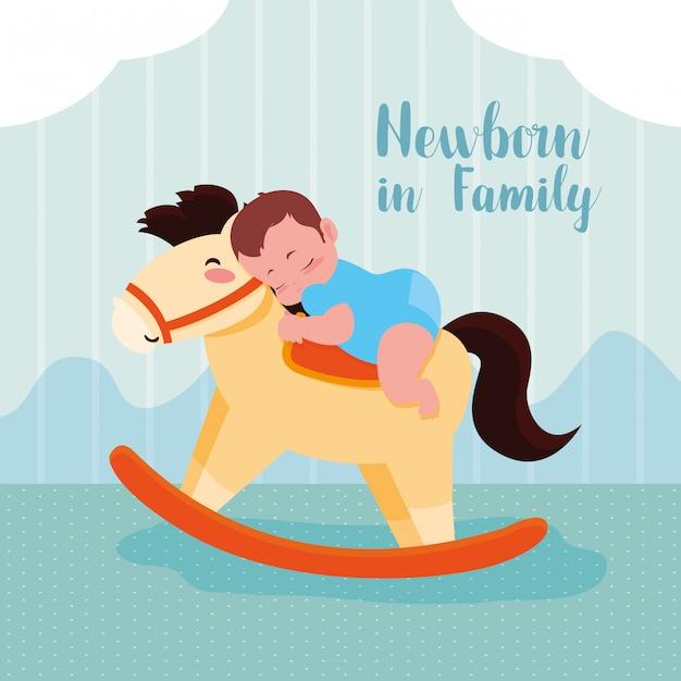 Nowonarodzona karta z chłopiec i drewnianym koniem Premium Wektorów