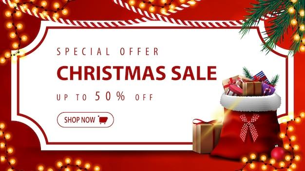 Oferta specjalna, wyprzedaż świąteczna, do 50% zniżki, czerwony baner rabatowy z białą kartką papieru w formie biletu w stylu vintage, gałęziami choinek, girlandami i torbą świętego mikołaja z prezentami Premium Wektorów