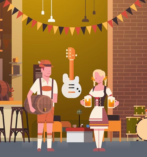 Para jest ubranym tradycyjnych ubrania w pubie pije piwo w prętowym oktoberfest przyjęcia świętowania kobiety i mężczyzna fest pojęciu Premium Wektorów