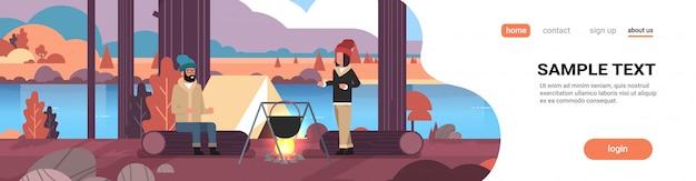 Para Turystów Mężczyzna Kobieta Gotowania Posiłków W Meloniku W Garnku Na Ognisku W Pobliżu Namiotu Kempingowego Camping Jesień Krajobraz Natura Rzeki Góry Premium Wektorów