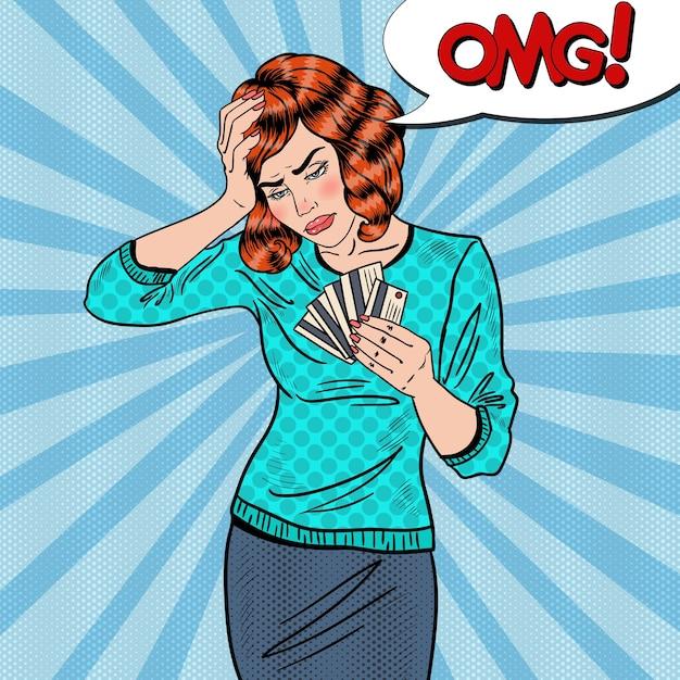 Pop Art Zdenerwowana Kobieta Z Kartami Kredytowymi Ma Ból Głowy. Premium Wektorów