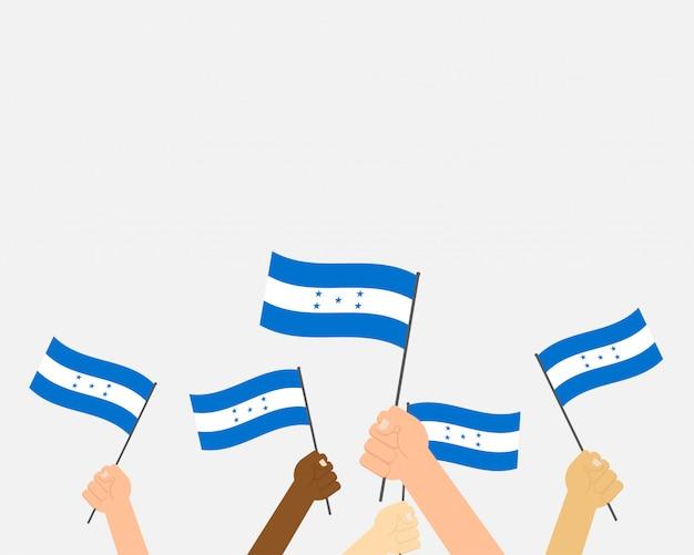 Ręce, trzymając flagi hondurasu Premium Wektorów