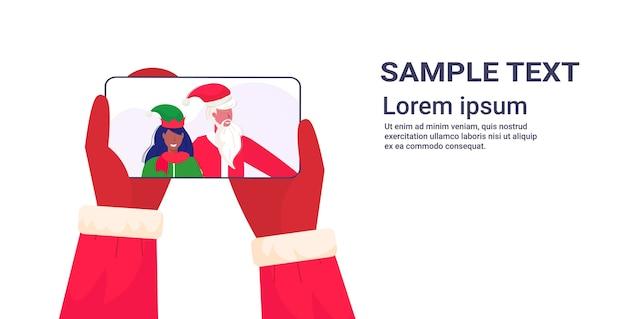Ręce Trzymając Smartfon święty Mikołaj Z Afroamerykańską Pomocniczką Elf Na Ekranie Koncepcja Uroczystości świątecznych Online Aplikacja Mobilna Portret Kopia Przestrzeń Ilustracja Premium Wektorów