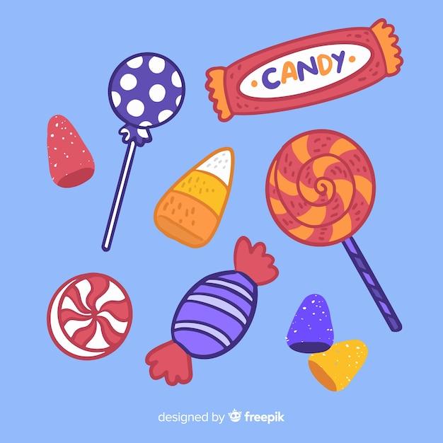 Ręcznie rysowane halloween kolekcja cukierków na niebieskim tle Darmowych Wektorów
