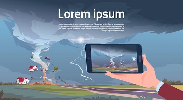 Ręka Trzymająca Tablet Filmowanie Przekręcanie Tornado Niszczenie Farmy Huragan Krajobraz Burzy Wodny Wodospad W Koncepcji Katastrofy Naturalnej Premium Wektorów