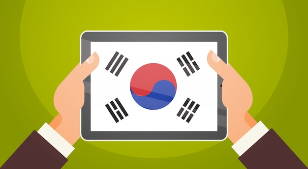 Ręki Trzyma Cyfrowej Pastylkę Z Południowym Korea Premium Wektorów