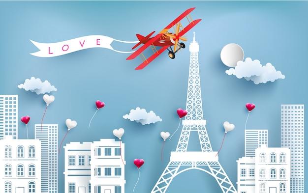 Samolot przewożący banery miłości latające nad miastem i wieże eiffla. Premium Wektorów