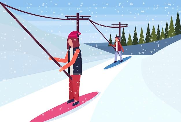 Snowboardziści Zjeżdżają Z Góry Za Pomocą Wyciągu Narciarskiego Premium Wektorów