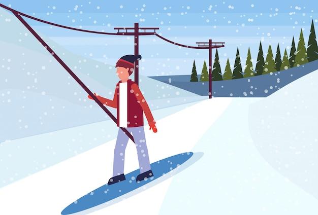 Snowboardzista Zjeżdżający Z Góry Za Pomocą Wyciągu Narciarskiego Premium Wektorów