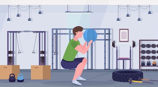 Sportowy Mężczyzna Robi Przysiady ćwiczenia Z Piłką Skóra Skórzana Facet Trening Cardio Trening Koncepcja Nowoczesna Siłownia Zdrowie Studio Klub Wnętrze Poziomej Pełnej Długości Premium Wektorów