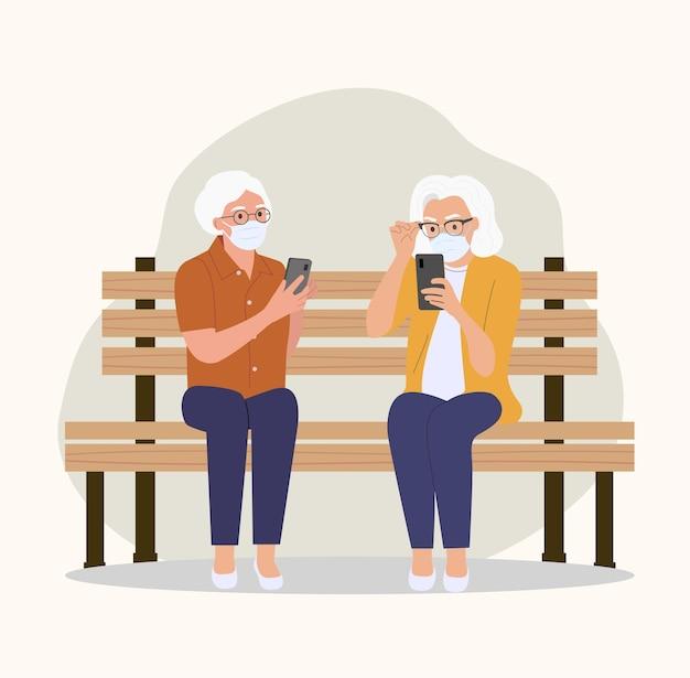 Starsze Kobiety W Maskach Siedzą Na ławce Ze Smartfonami. Ilustracja Stylu Płaskiej Kreskówki Premium Wektorów