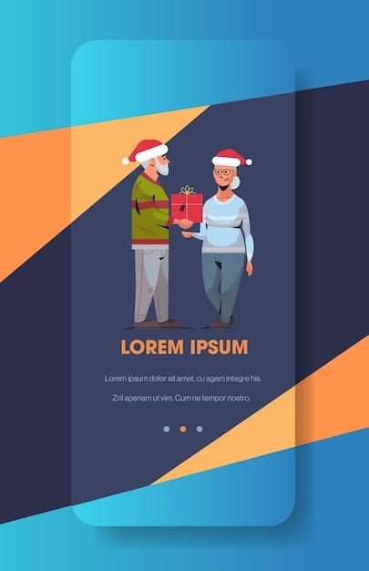 Starszy Mężczyzna W Czapce Mikołaja Wręczający Prezent Pudełko Dojrzałej Kobiecie Rodzina świętuje Wesołych świąt Szczęśliwego Nowego Roku Ferie Zimowe Koncepcja Ekran Smartfona Aplikacja Mobilna Online W Pionie Premium Wektorów